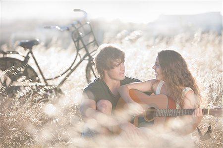 Woman playing guitar for boyfriend Stock Photo - Premium Royalty-Free, Code: 649-06488544