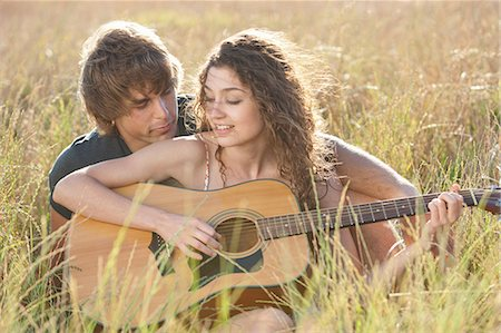 Couple playing guitar in tall grass Stock Photo - Premium Royalty-Free, Code: 649-06488560