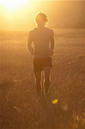 Man running in tall grass at sunset Stock Photo - Premium Royalty-Free, Code: 649-06488585