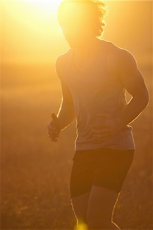 fit people - Man running in tall grass at sunset Stock Photo - Premium Royalty-Free, Code: 649-06488586
