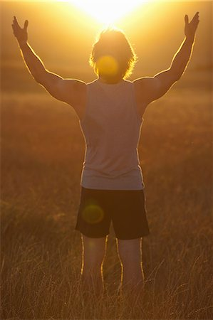 Man standing in field at sunset Stock Photo - Premium Royalty-Free, Code: 649-06488587