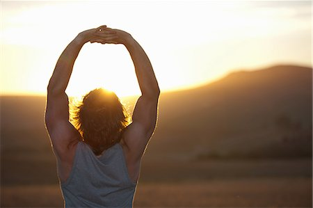 Man stretching in field at sunset Stock Photo - Premium Royalty-Free, Code: 649-06488589