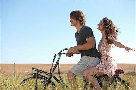 Couple riding bicycle in tall grass Stock Photo - Premium Royalty-Free, Code: 649-06488581