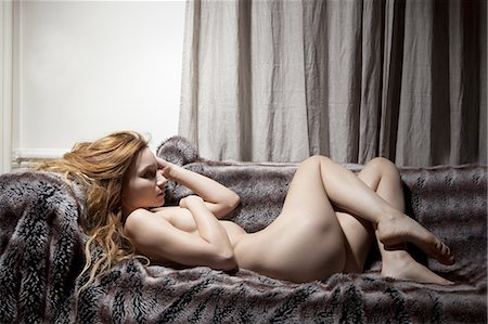 Nude woman laying on fur blanket Stock Photo - Premium Royalty-Free, Code: 649-06488595
