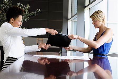 Businesswomen fighting over folder Stock Photo - Premium Royalty-Free, Code: 649-06488758
