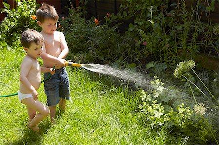 Boys watering plants in garden Stock Photo - Premium Royalty-Free, Code: 649-06488924