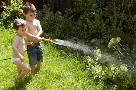Boys watering plants in garden Stock Photo - Premium Royalty-Free, Code: 649-06488924