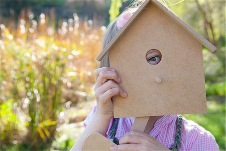Girl peeking through birdhouse Stock Photo - Premium Royalty-Free, Code: 649-06489036