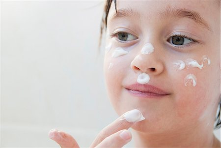 Girl rubbing moisturizer on her face Stock Photo - Premium Royalty-Free, Code: 649-06489050