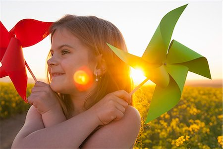 sun - Girl playing with pinwheels outdoors Stock Photo - Premium Royalty-Free, Code: 649-06489098