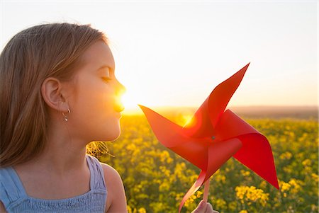 Girl playing with pinwheel outdoors Stock Photo - Premium Royalty-Free, Code: 649-06489099