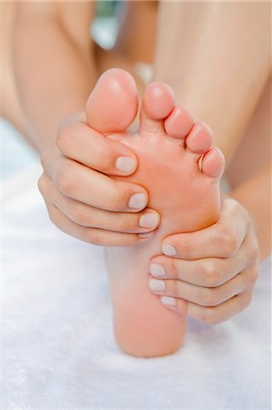 foot massage - Close up of woman rubbing her foot Stock Photo - Premium Royalty-Free, Code: 649-06489174