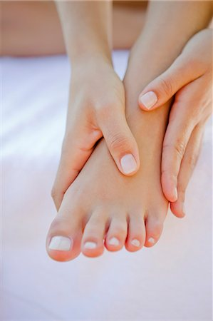 foot massage - Close up of woman rubbing her foot Stock Photo - Premium Royalty-Free, Code: 649-06489173