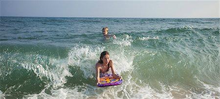 preteen swim - Girl riding wave on boogie board Stock Photo - Premium Royalty-Free, Code: 649-06489235