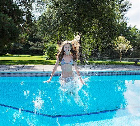 Girl jumping into swimming pool Stock Photo - Premium Royalty-Free, Code: 649-06489237