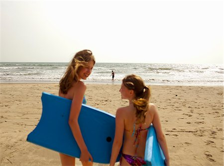 Girls carrying boogie boards on beach Stock Photo - Premium Royalty-Free, Code: 649-06489244