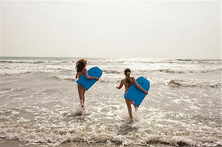 Girls carrying boogie boards in waves Stock Photo - Premium Royalty-Free, Code: 649-06489245