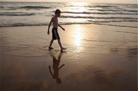 Boy walking in waves on beach Stock Photo - Premium Royalty-Free, Code: 649-06489241