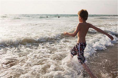 Boy walking in waves on beach Stock Photo - Premium Royalty-Free, Code: 649-06489242