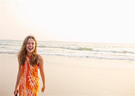 preteen asian girls - Smiling girl walking on beach Stock Photo - Premium Royalty-Free, Code: 649-06489243