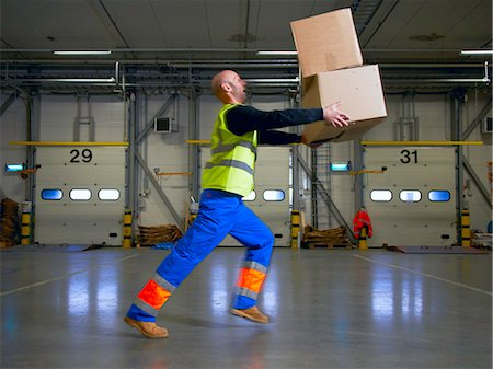 Worker balancing boxes in warehouse Stock Photo - Premium Royalty-Free, Code: 649-06489258