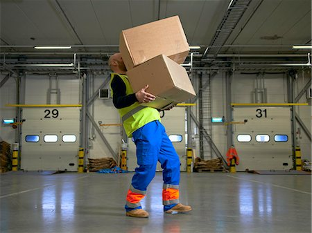 Worker carrying boxes in warehouse Stock Photo - Premium Royalty-Free, Code: 649-06489259
