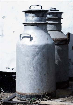 Milk jugs sitting outside building Stock Photo - Premium Royalty-Free, Code: 649-06489356