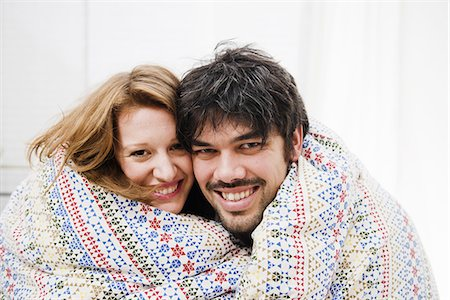 Smiling couple wrapped in blanket Stock Photo - Premium Royalty-Free, Code: 649-06489379
