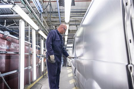 Worker inspecting vehicle in car factory Stock Photo - Premium Royalty-Free, Code: 649-06489515