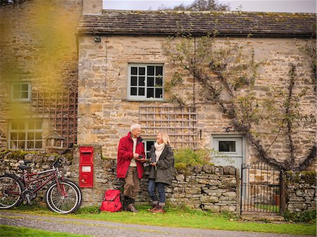 Older couple by stone wall in village Stock Photo - Premium Royalty-Free, Code: 649-06489541