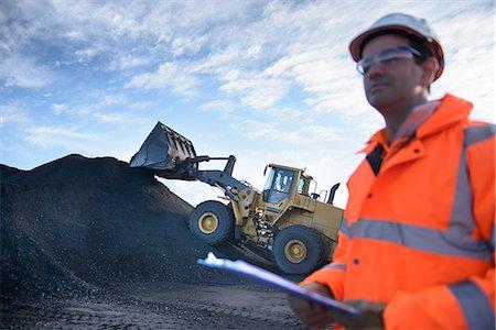 Excavator and worker at coal mine Stock Photo - Premium Royalty-Free, Code: 649-06489598