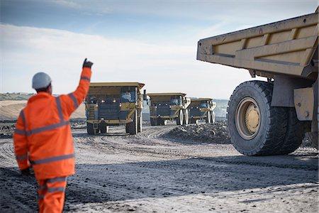 Worker directing trucks at surface mine Stock Photo - Premium Royalty-Free, Code: 649-06489607