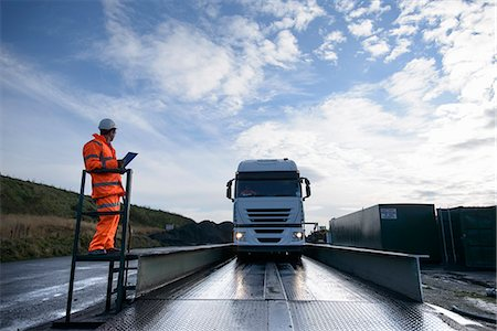 Worker directing truck on scales Stock Photo - Premium Royalty-Free, Code: 649-06489611