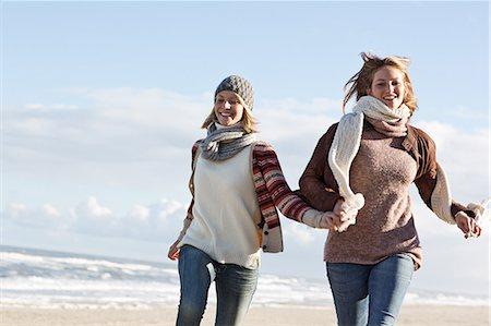 Smiling women running on beach Stock Photo - Premium Royalty-Free, Code: 649-06489713