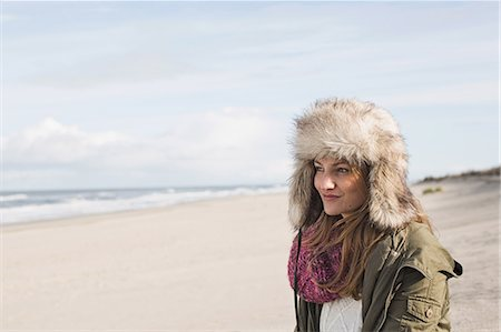 fur - Smiling woman standing on beach Stock Photo - Premium Royalty-Free, Code: 649-06489760