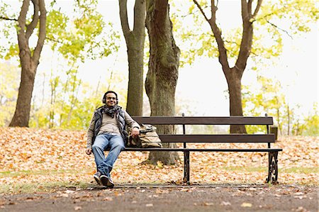 people sitting on bench - Smiling man sitting on park bench Stock Photo - Premium Royalty-Free, Code: 649-06489832