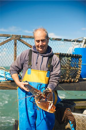 Fisherman holding lobster on boat Stock Photo - Premium Royalty-Free, Code: 649-06489865