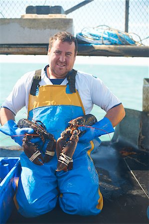 Fisherman holding lobsters on boat Stock Photo - Premium Royalty-Free, Code: 649-06489866