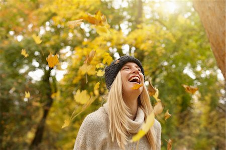 Woman playing in autumn leaves outdoors Stock Photo - Premium Royalty-Free, Code: 649-06489880