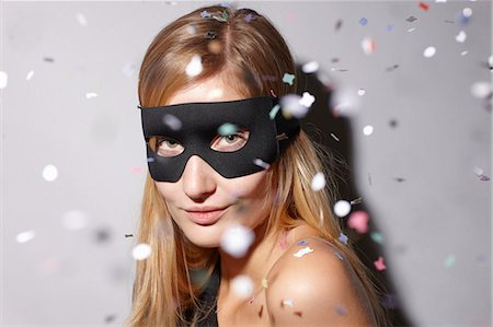 Woman wearing mask in confetti Stock Photo - Premium Royalty-Free, Code: 649-06489899