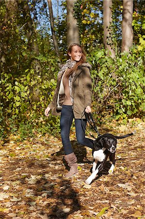 Woman walking dog in forest Stock Photo - Premium Royalty-Free, Code: 649-06489919