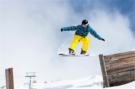 sports and snowboarding - Snowboarder jumping off wooden fence Stock Photo - Premium Royalty-Free, Code: 649-06490027