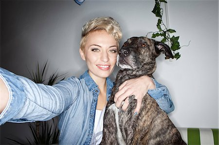 Smiling woman taking picture with dog Stock Photo - Premium Royalty-Free, Code: 649-06490065