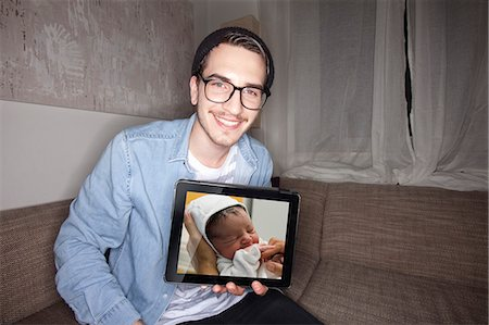 showing - Man with newborn on tablet computer Stock Photo - Premium Royalty-Free, Code: 649-06490083