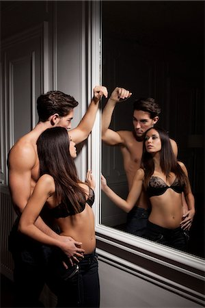 Couple admiring themselves in mirror Stock Photo - Premium Royalty-Free, Code: 649-06532539