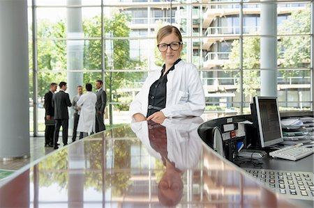 people hospital - Doctor leaning on secretarys desk Stock Photo - Premium Royalty-Free, Code: 649-06532626
