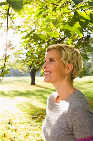 Woman smiling in park Stock Photo - Premium Royalty-Free, Code: 649-06532674