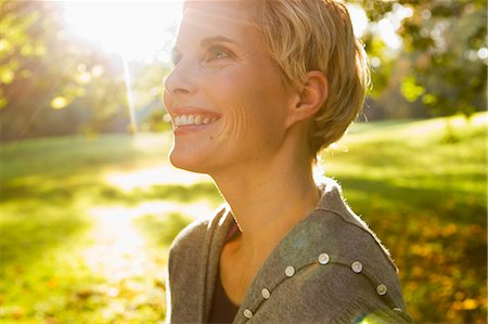 sun - Woman smiling in park Stock Photo - Premium Royalty-Free, Code: 649-06532681