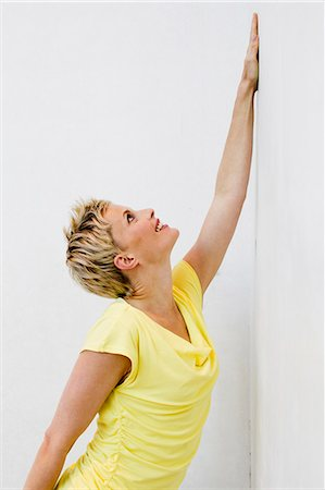 Smiling woman wearing yellow shirt Stock Photo - Premium Royalty-Free, Code: 649-06532716