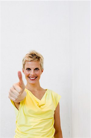 Smiling woman giving 'thumbs up Stock Photo - Premium Royalty-Free, Code: 649-06532717